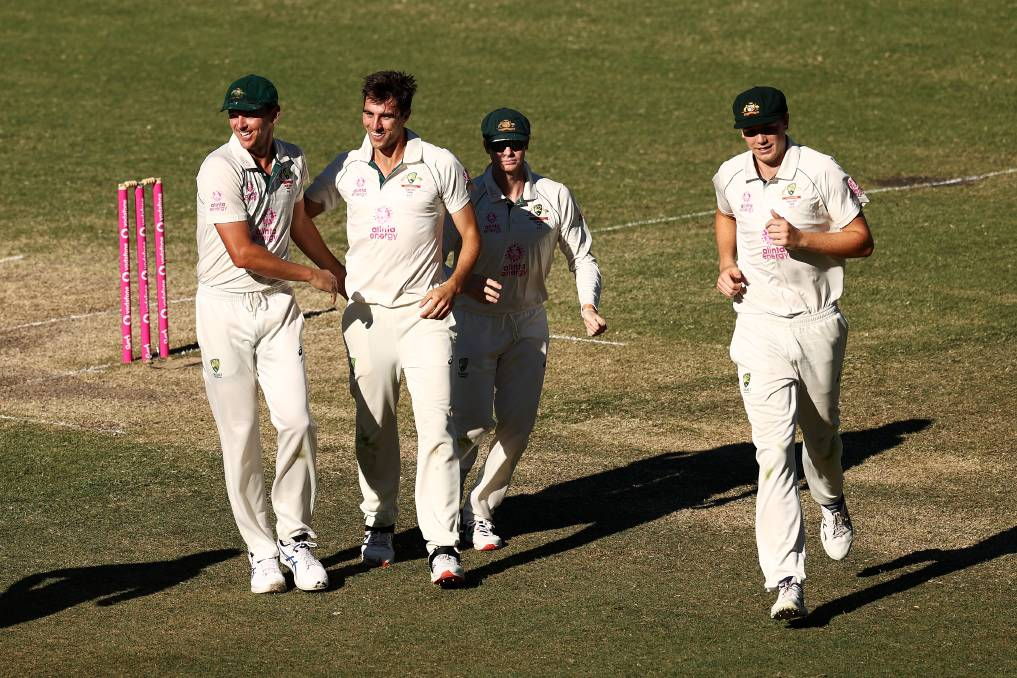 Australia's Pat Cummins celebrates with his teammates after dismissing Rohit Sharma. Photo: Cameron Spencer/Getty Images