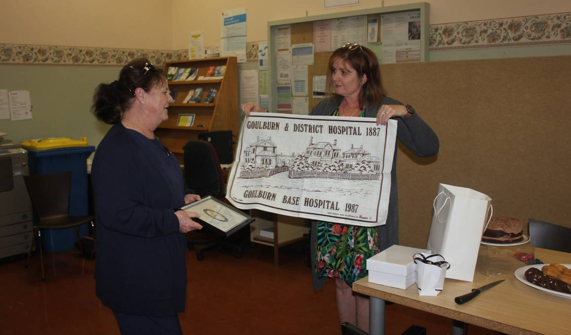 Rhonda Craig receiving a Goulburn Base Hospital tea towel from acting director of nursing and midwifery Cheryl Tozer. Photo: Burney Wong.